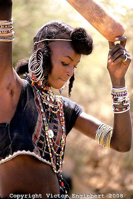 Niger. Sahel. Wodaabe (Bororo/Fulani) nomad woman pounding millet.