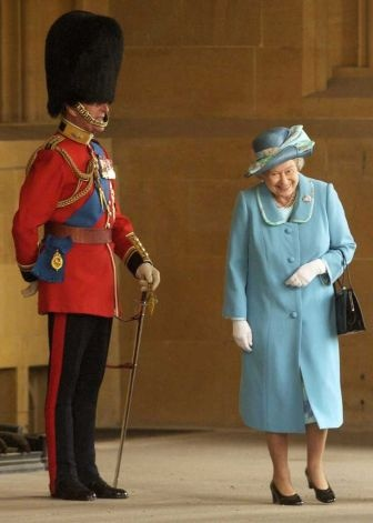 Queen Elizabeth giggling at Prince Philip, prior to The Queen's Company Grenadier Guards ceremonial review at Windsor Castle, April 15, 2003.  (this is a very cute photo!)