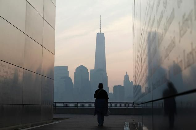 Woman looks out at new york s lower manhattan and 1 world trade