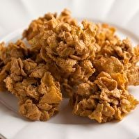 Peanut Butter Cornflake ingredients 1 Cup Sugar 1 Cup Corn Syrup 1 1/2 Cups Peanut Butter 5 Cups Cornflakes directions In a saucepan bring Sugar and Corn Syrup to a boil. Remove from heat and stir in Peanut Butter. Stir until Melted and smooth. Stir in cornflakes and mix well. Mixture will be stiff. Drop by spoonfuls onto wax paper lined cookie sheet