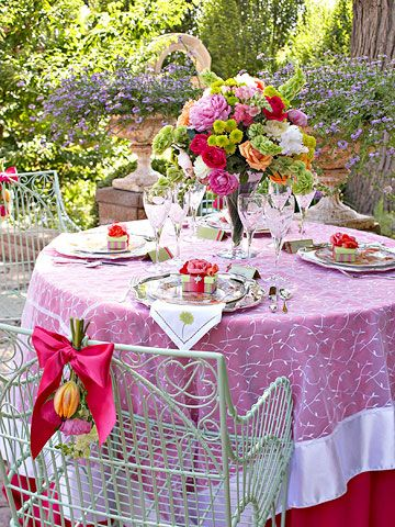 A garden party in June: embroidered linens, floral plates, silver chargers and flatware; roses, spray mum, snapdragons, dahlias, bells of Ireland, and peonies.
