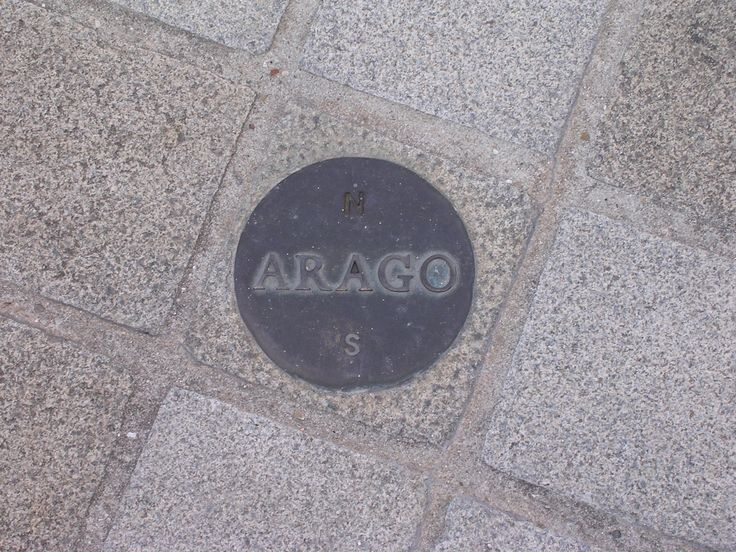 """Arago medallion near the Louvre pyramid. In his  """"Hommage à Arago,"""" commissioned as a memorial to François Arago (1786-1853), Jan Dibbets set over a hundred of these bronze medallions into the ground along the Paris Meridian from the southern to the northern boundaries of the City. Each of them is 12 cm in diameter, with Arago's name and showing north and south.  (Photo credit: Poulpy)"""
