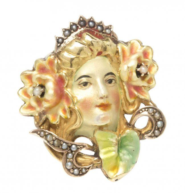 An Art Nouveau Gold, Polychrome Enamel, and Seed Pearl Pin, depicting a female facade within a foliate surround accented with seed pearls and applied yellow, green and pink enamel. 3.70 dwts.