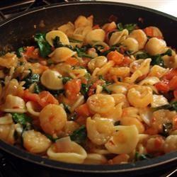 A spicy shrimp, tomato, and spinach sauce tops orecchiette pasta.