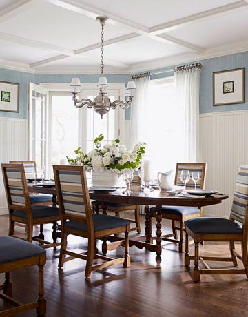 Designed by Marshall Watson, this Hampton's dining room features great striped fabric on the chairs and a blue-gray color on the walls.