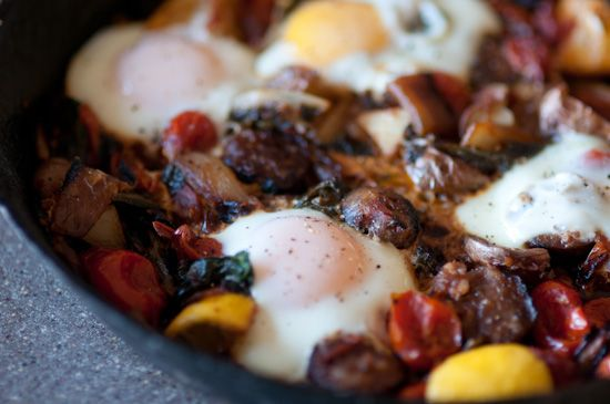 Poached eggs over braised tomatoes with sausage and chard. A healthy ...