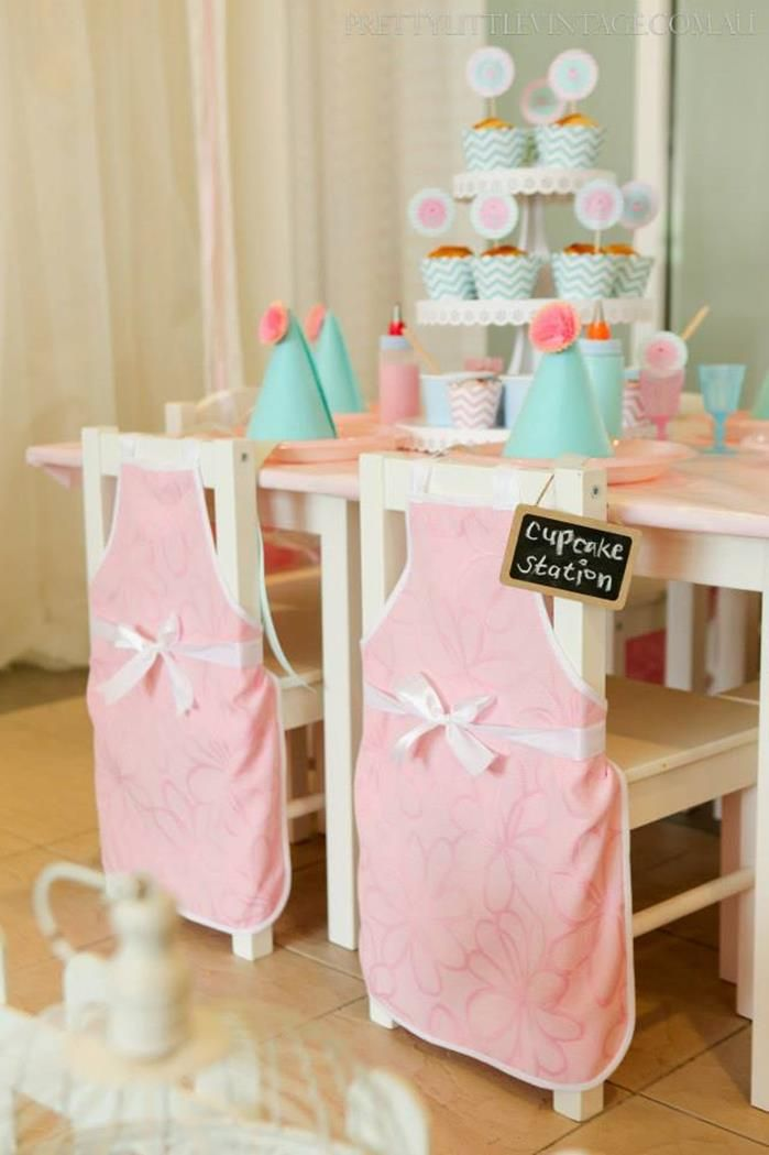 Aprons on the backs of chairs! Cupcake Shoppe 1st Birthday Party with Lots of Really Cute Ideas via Kara's Party Ideas KarasPartyIdeas.com #CupcakeStand #Party #Ideas #Supplies #cupcakeparty #cupcake #chairs #aprons