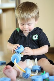 """Really good fine motor skill for toddler with teeny hands. A lacing activity using a foam noodle as the """"beads."""""""