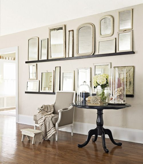 a gallery-esque wall of vintage framed mirrors across picture ledges