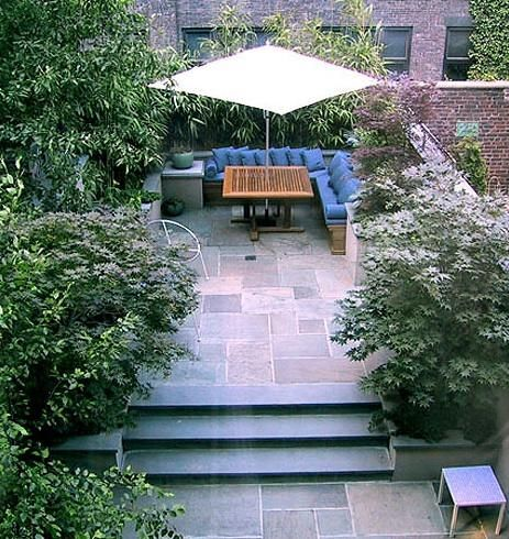 A garden in New York designed by LA-based Elysian Landscapes found on remodelista.com  Tall lush plants surround this garden space with natural stone pavers and planter boxes.