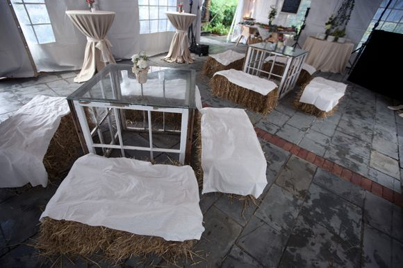 Love the tables made from upcycled windows and the hay bale seating.