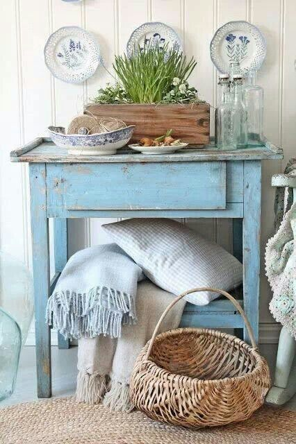 Rustic blue table with plates behind and spring bulbs and inspiring objets d'art