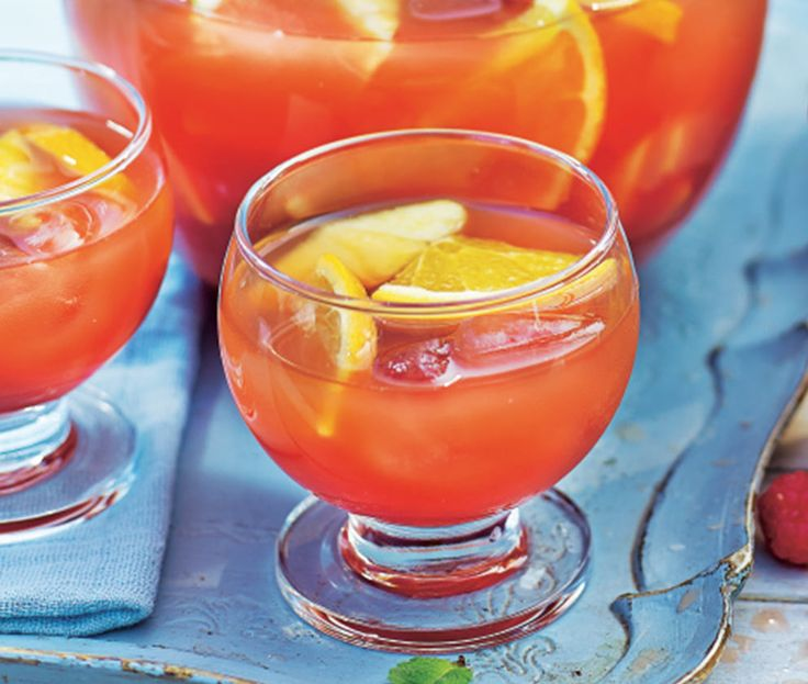 Glass of orange rum punch with slices of lemon