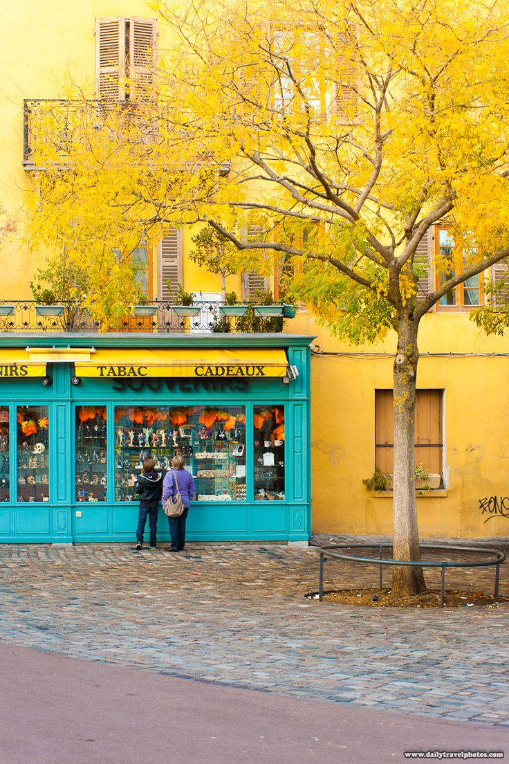 A yellow building complements the fall tree leaves near the center of old town in Annecy, France.