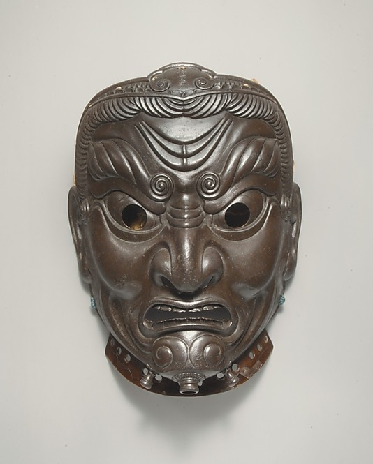 Myochin Muneakira (Edo Period, 1673–1745) - Menpo (Face Armour), Mask. Dated 1745. Lacquered Iron. The Armorer's Masterpiece, this Mask by Muneakira was already Famous when it was Reproduced in a Woodcut Book Illustration in 1763. The Mask Represents Jikokuten, Guardian of the East––one of the Four Kings of Heaven. The Mask retains its Original Silk Head Covering sewn to the upper edges. Front View. Signed on Chin. The Metropolitan Museum of Art, New York.
