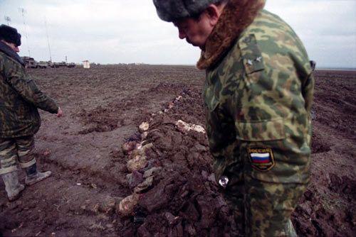 Подполковник российской армии рассматривает головы убитых людей