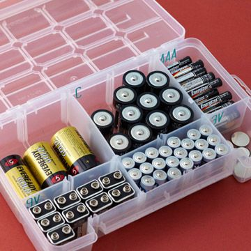 Batteries:   A plastic tackle box with multiple sizes of openings to hold batteries, grouped by size.