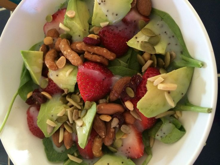 Spinach salad with avocado strawberries sesame sticks and seeds with ...
