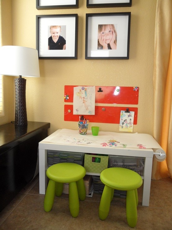 I did it!! So loving the art area I made for the kids.  In a corner of the family room I added a Lack coffee table (IKEA), attached a micro curtain rod from Bed Bath and Beyond (on clearance), IKEA Mala paper roll, 2 green Mammut stools (IKEA),  2 orange magnet boards (IKEA- last chance), and cute plastic containers from Target. dbbydk