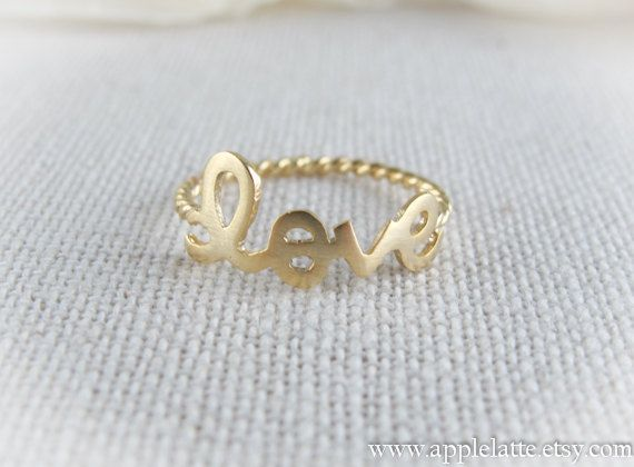 gold love ring with twisted ringband  via Etsy.