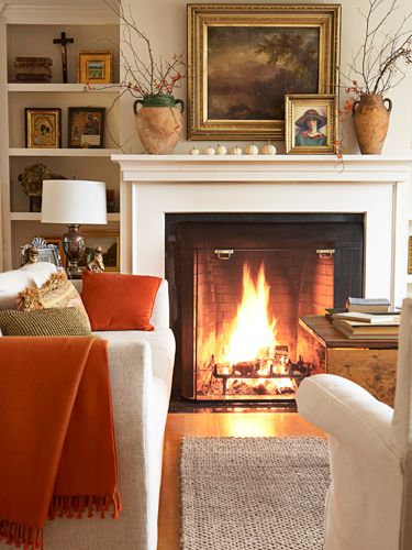 A roaring fire takes center stage in the living room of this New Hampshire home, furnished with a nubby cream sofa and white slipcovered chairs, both from Crate & Barrel.