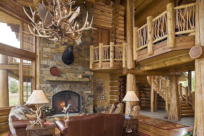 Great room of log home....moose on the fireplace and moose antler chandelier