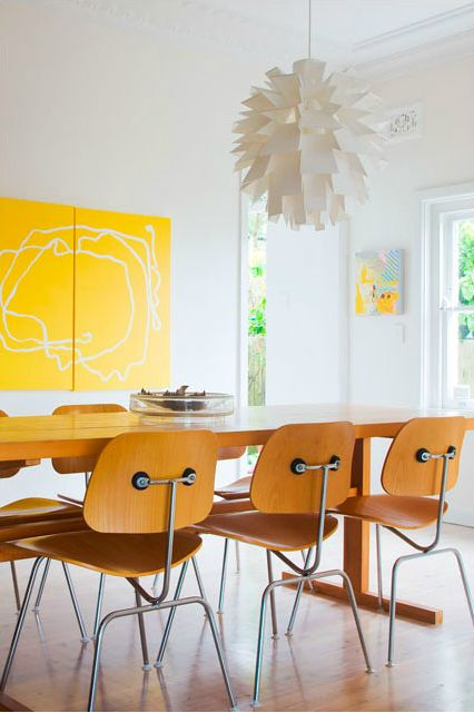 I love this dining room. Nice pendant lamp, modern art and a set of Eames DCM chairs.  photographer Simon Whitbread