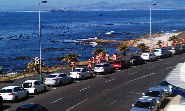 Half naked men run in Green Point