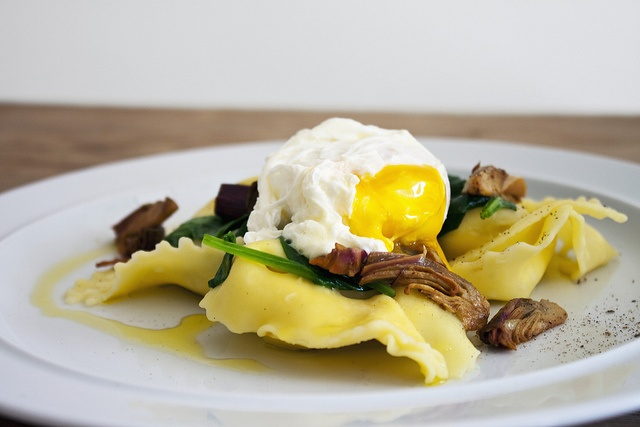 Ravioli with poached egg, spinach and artichoke