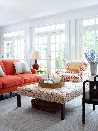 living room with upholstered coffee table, color palette of coral and pale blue