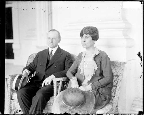 1924. Half-length portrait of President and Mrs. Calvin Coolidge (nee Grace Anna Goodhue) sitting in wicker chairs on the porch of the White House in Washington, D. C.