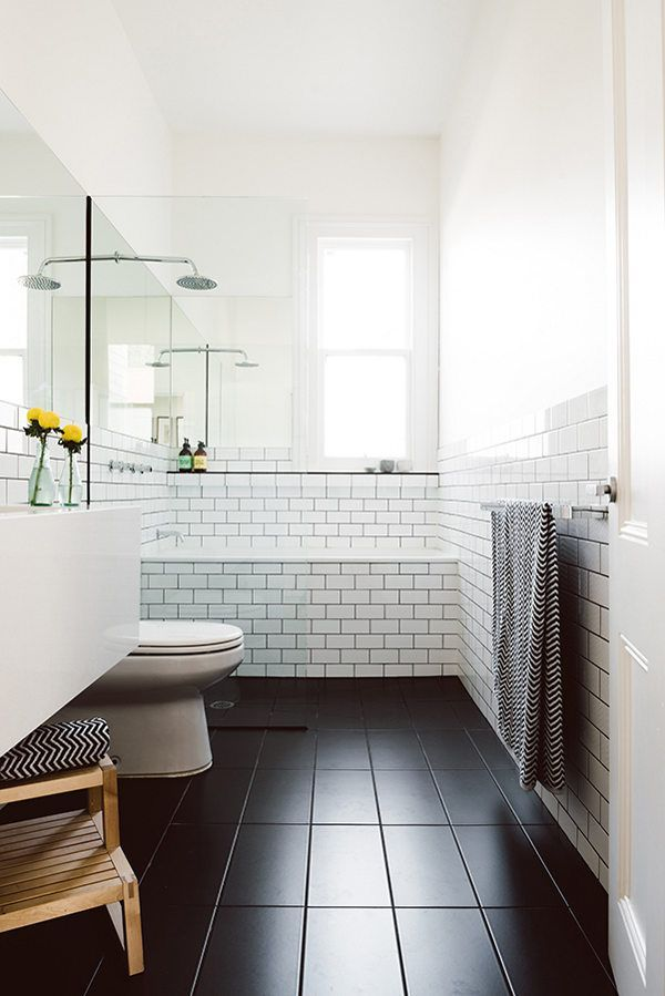 Dark tile floor and subway tile wall. White tiles with dark grout.