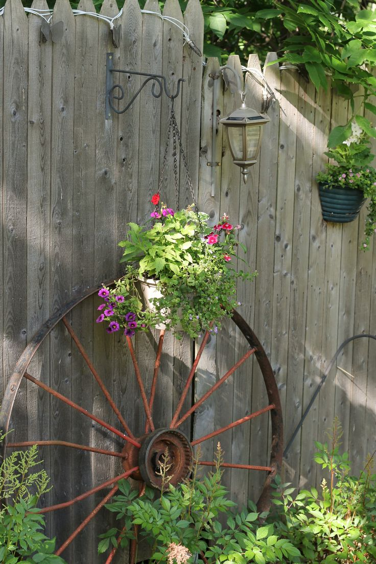 Old wagon wheel up against an old rustic fence.