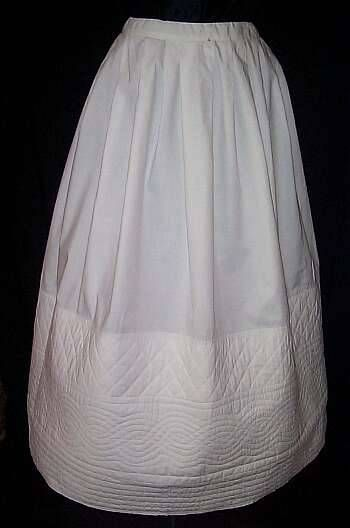 C.1865. Quilted petticoats are quite unusual to find due to the amount of work that went into making them and the fact that central heating did not exist, so they were often worn out.  This lovely petticoat is in wonderful condition and is made out of white cotton. The bottom half of the skirt had wadding inserted into it and then decorative stitches were used to keep it in place. The stitching was done with an old chain stitch treadle machine which is common for the mid 1860's.