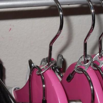 """Photo: That's a Hang Up.  I love double hangers for hanging pants and shirts together as well as skirts and blouses.  No need to buy those expensive """"piggyback"""" hooks, just pop a soda can and use that."""