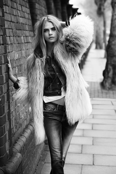 Cara Delevingne in a super cool layered outfit. White shirt, denim jacket, skinny jeans, big faux fur jacket.
