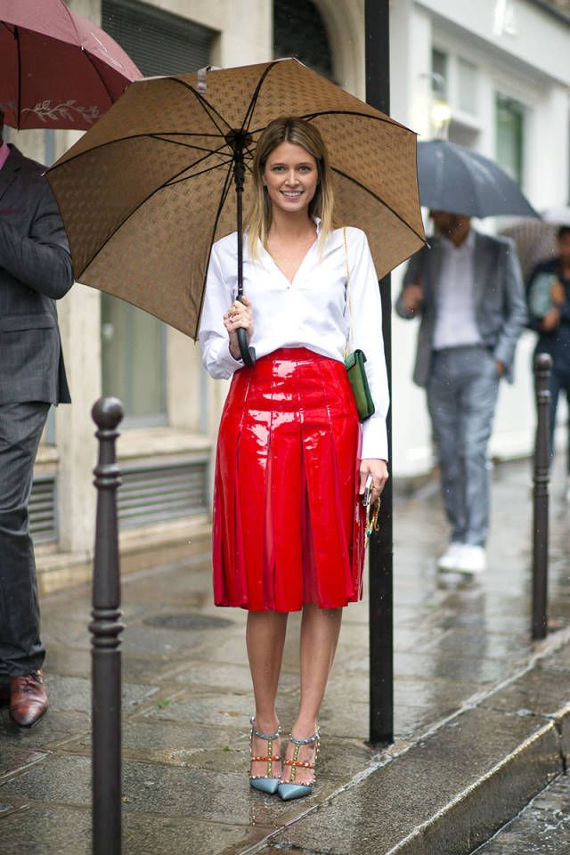 This street style shot proves that you can still dress stylish in the rain // crisp white blouse + red shiny skirt