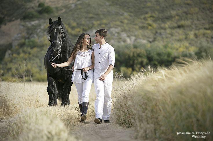 Novios paseando por el campo con su caballo durante su sesión de fotografía preboda en Toledo