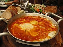 ... eggs poached in a sauce of tomatoes, chili peppers, onions, often