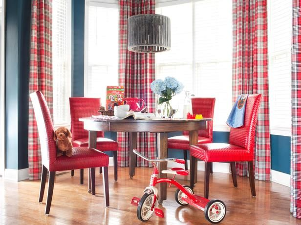 The playful breakfast nook is packed with vibrant hues and graphic lines. The walls were painted the same shade of navy blue as the family room area, and the windows are covered with the same drapery fabric and hardware, keeping the different spaces united for a cohesive look.