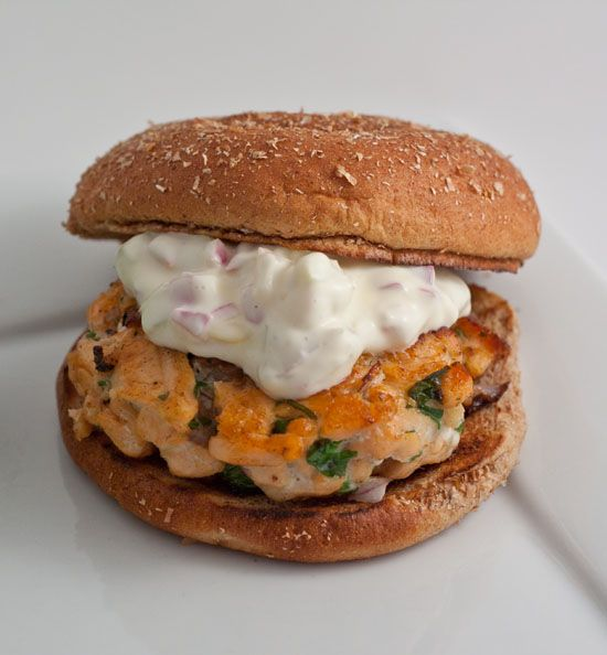... salmon burger in a cast iron skillet topped with homemade tartar sauce