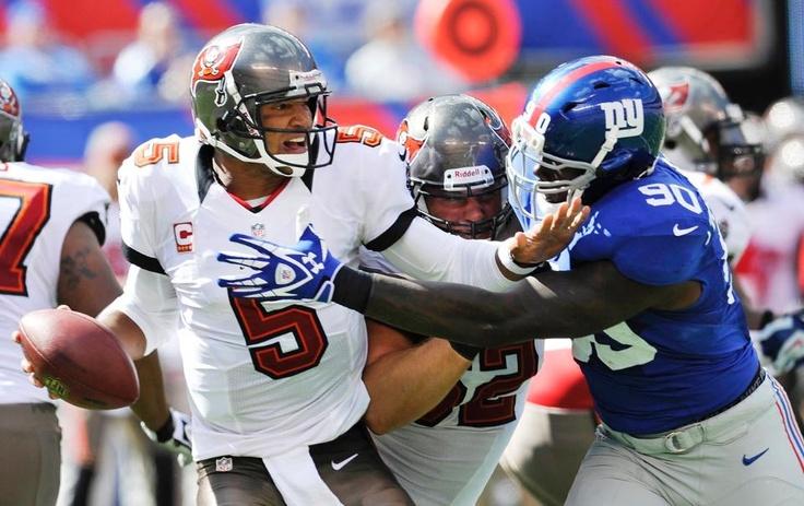 Tampa Bay Buccaneers QB Josh Freeman looks to pass away from New York Giants DE Jason Pierre-Paul during the first half.