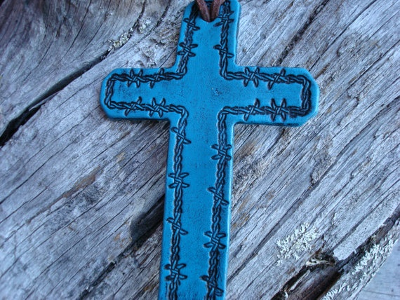 Turquoise colored saddle cross featuring barbed wire stamping.