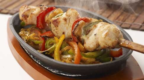 of tender chicken interspersed with green, red and yellow peppers ...