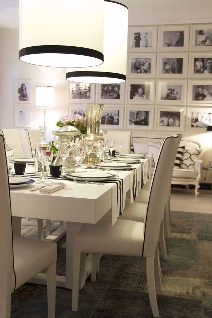 beautiful black and white styled dinning room with black and white photo wall.  the white frames on the white wall look fantastic