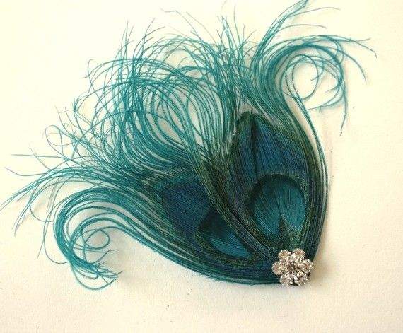 This hairclip was handcrafted using beautiful teal peacock feathers and a crystal button. It has an alligator clip attached to the back for securing it into your hair.
