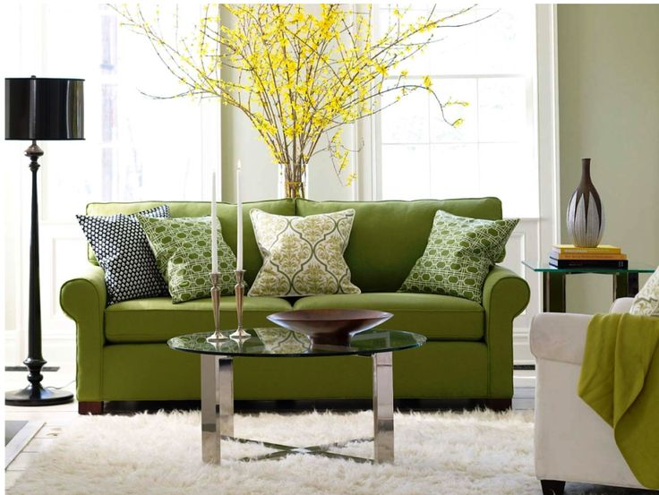 Forsythia branches in a vase behind green sofa with graphic print pillows set on a cream shag rug Love how it is all pulled together with touches of green black and cream