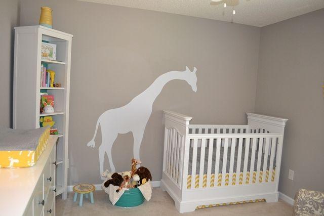 Love the giraffe peeking over the crib in this sweet gray and yellow nursery. #nursery