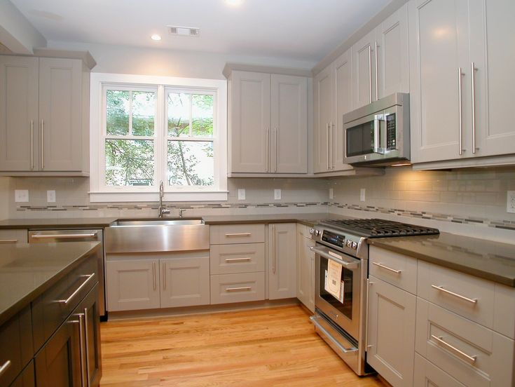 kitchen features gray cabinets with modern pulls, quartz countertops ...
