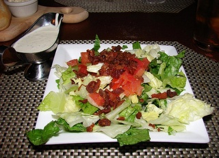 Malone's Lexingtonian house salad copycat recipe-  Salad Ingredients:    4 slices bacon, cooked crisp and crumbled  2-3 cups romaine and iceberg lettuce mix  1.5 ounces dices tomatoes    Dressing Ingredients:    1 16 ounce container sour cream  1 packet ranch dip mix  1/8 teaspoon dry mustard  2 cups mayonnaise  1/2 cup buttermilk  1/2 cup whole milk